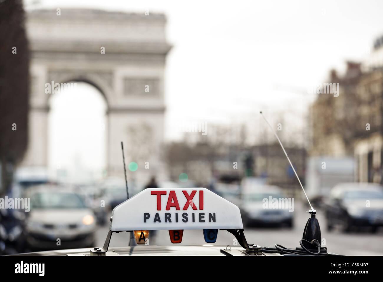 Taxi de París por el Arc de Triomphe Imagen De Stock