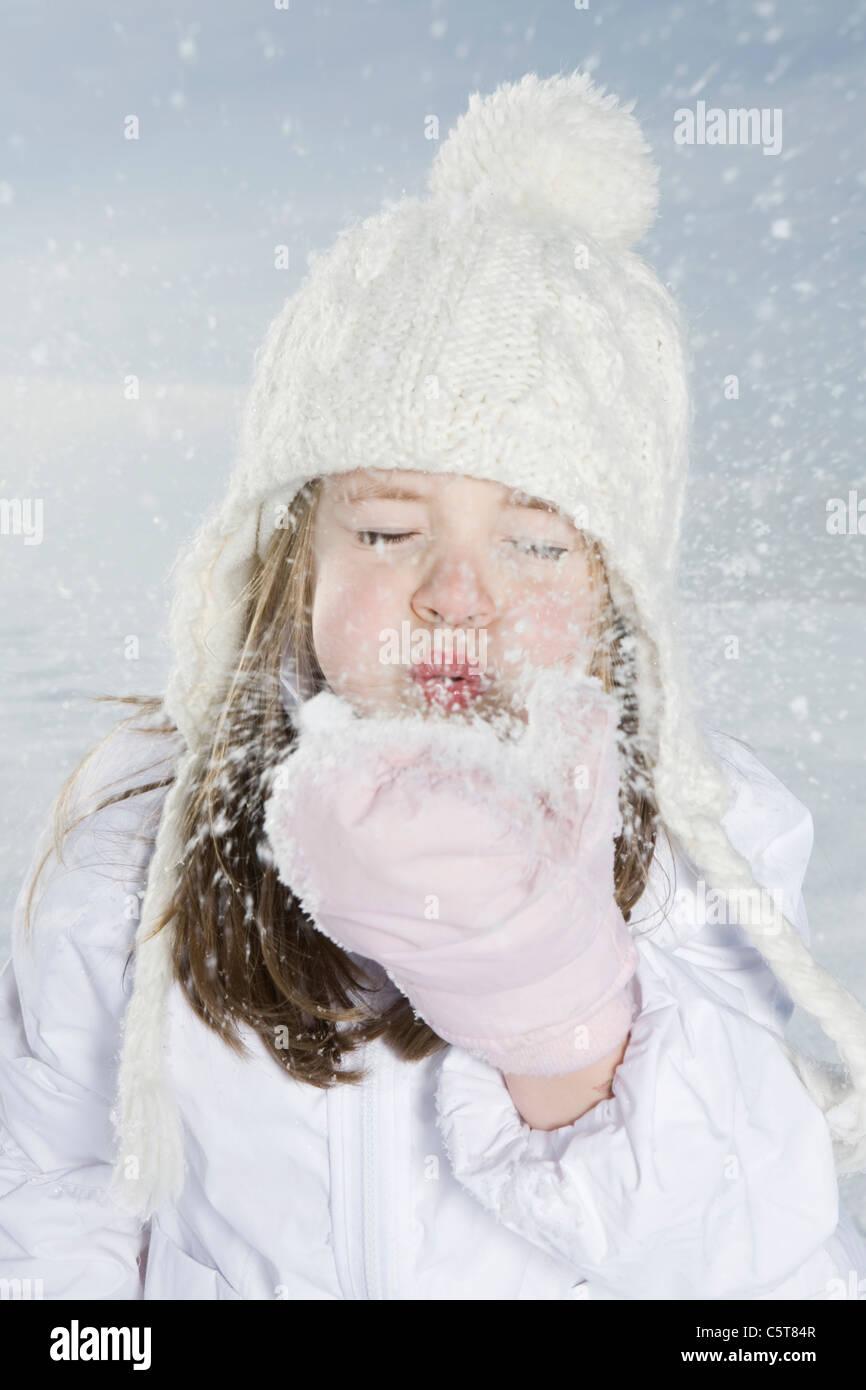 Alemania, Baviera, Munich, Chica (4-5) el soplado de nieve fuera de mano, los ojos cerrados, Retrato Imagen De Stock