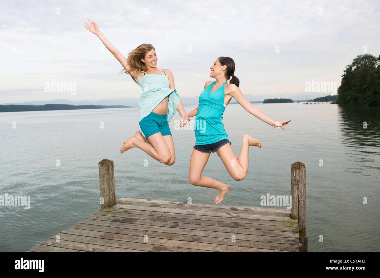 Alemania, Baviera, Starnberger See, dos mujeres jóvenes saltando sobre jetty, riendo, Retrato Imagen De Stock