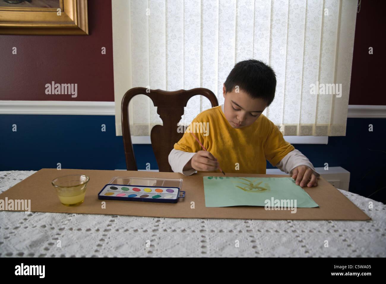 Niño de 6 años de pintar una imagen en la mesa de comedor Imagen De Stock