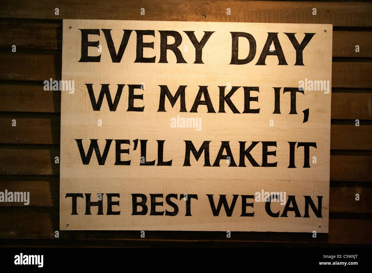 Cada día hacemos bien hacer lo mejor que podamos placa de madera en la oficina original en la destilería Imagen De Stock