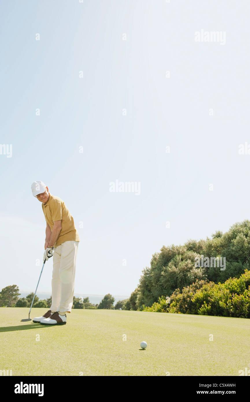 España, Mallorca, Senior hombre jugando al golf, vista lateral Imagen De Stock