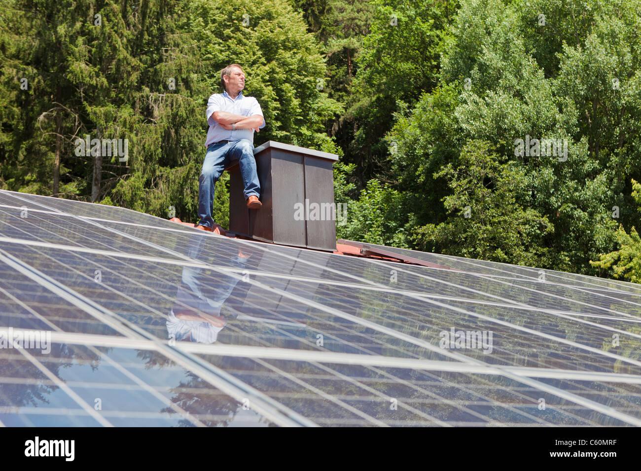 Hombre de pie sobre el techo con paneles solares Imagen De Stock