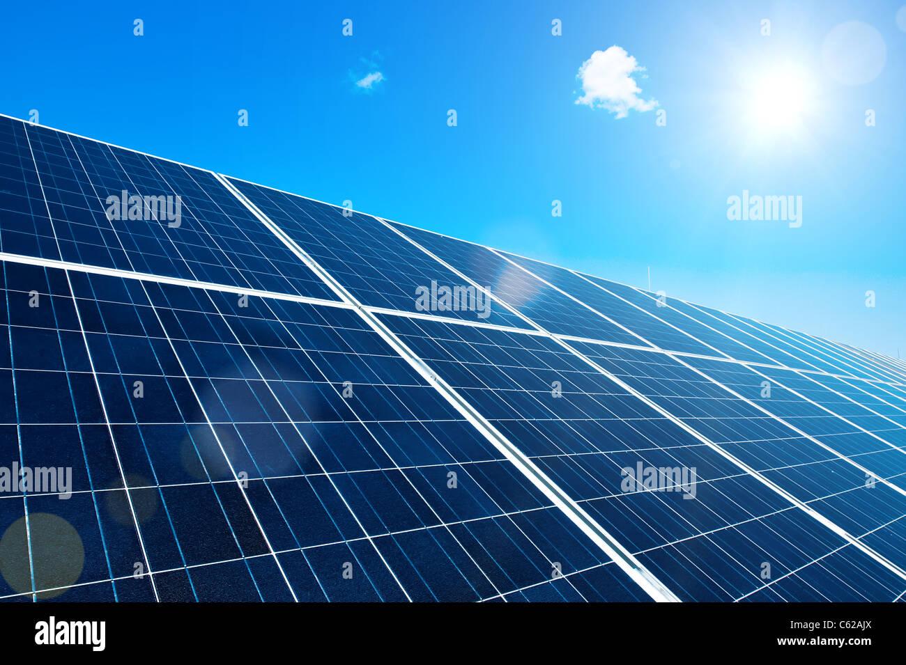 Panel solar con sol y cielo azul y destellos de lente Imagen De Stock