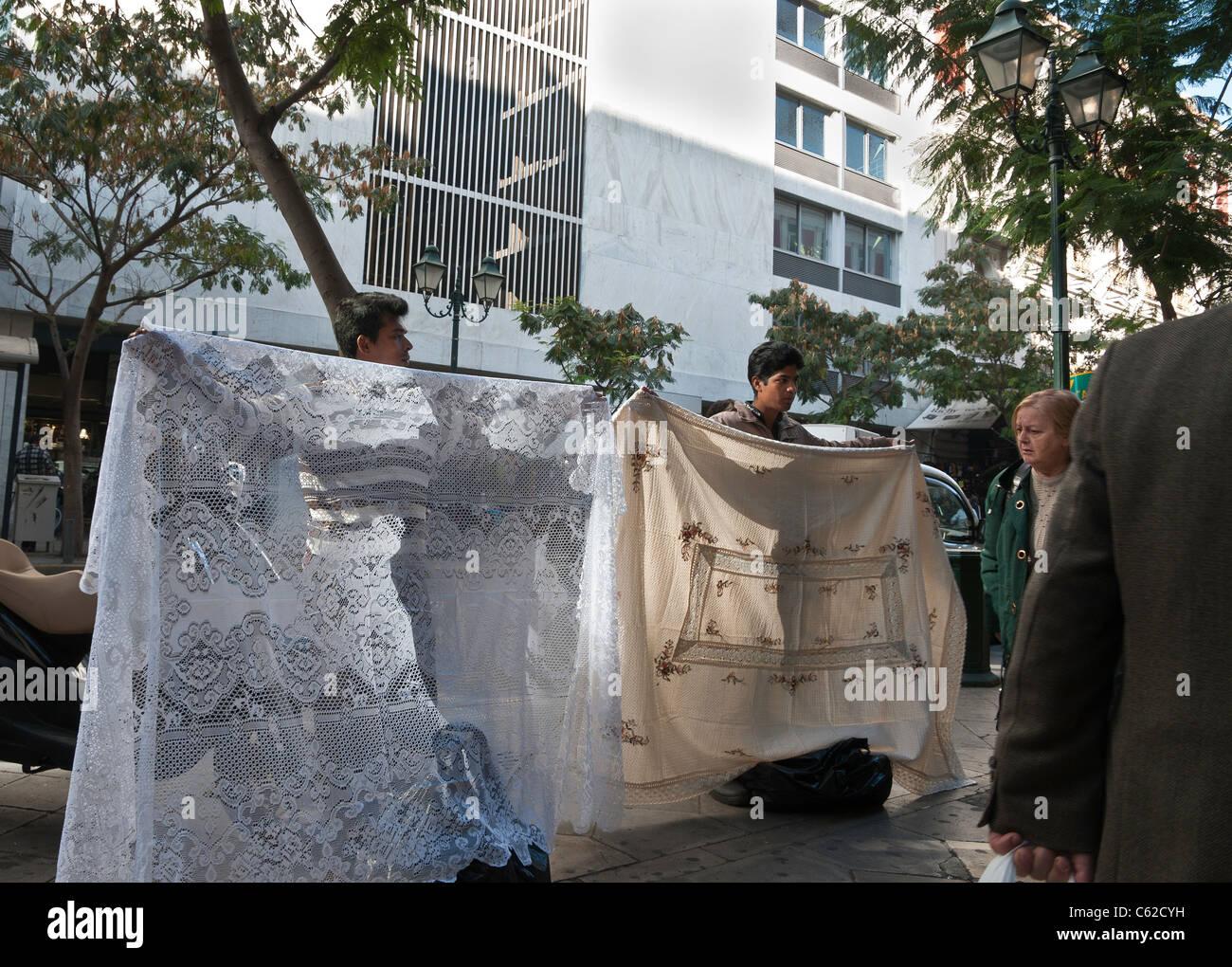 Los inmigrantes que venden manteles en Athinas Street, en el centro de Atenas, Grecia Foto de stock
