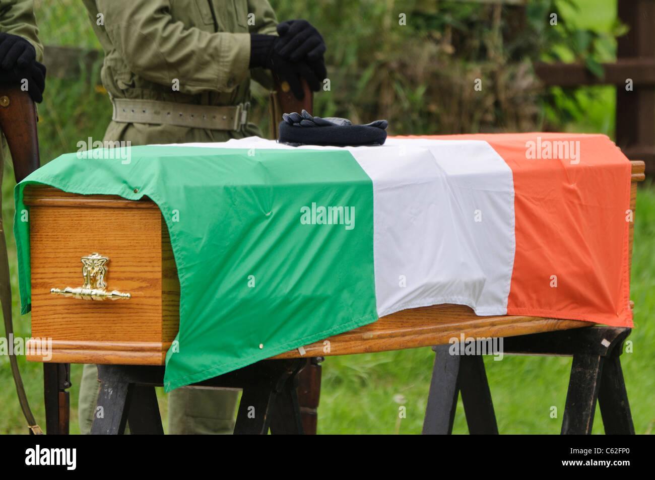 IRA guantes de paramilitares y boina en un ataúd con una bandera tricolor  irlandesa. El hombre de la IRA en segundo plano. bb3d12b3934