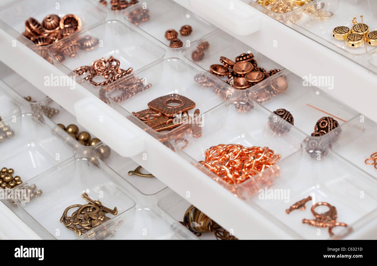 ce143aefc83e Pequeñas piezas metálicas utilizadas para crear joyas hechas en casa y se  almacenan en cajones de