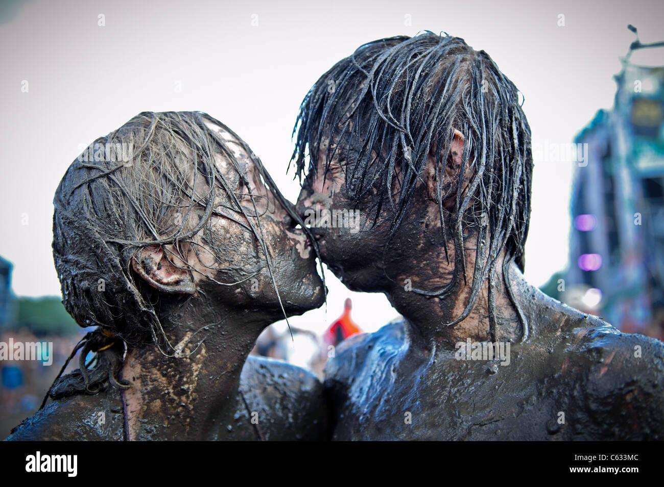 Joven pareja besándose cubierto de barro en el Przystanek Woodstock - al aire libre más grande de Europa festival Foto de stock