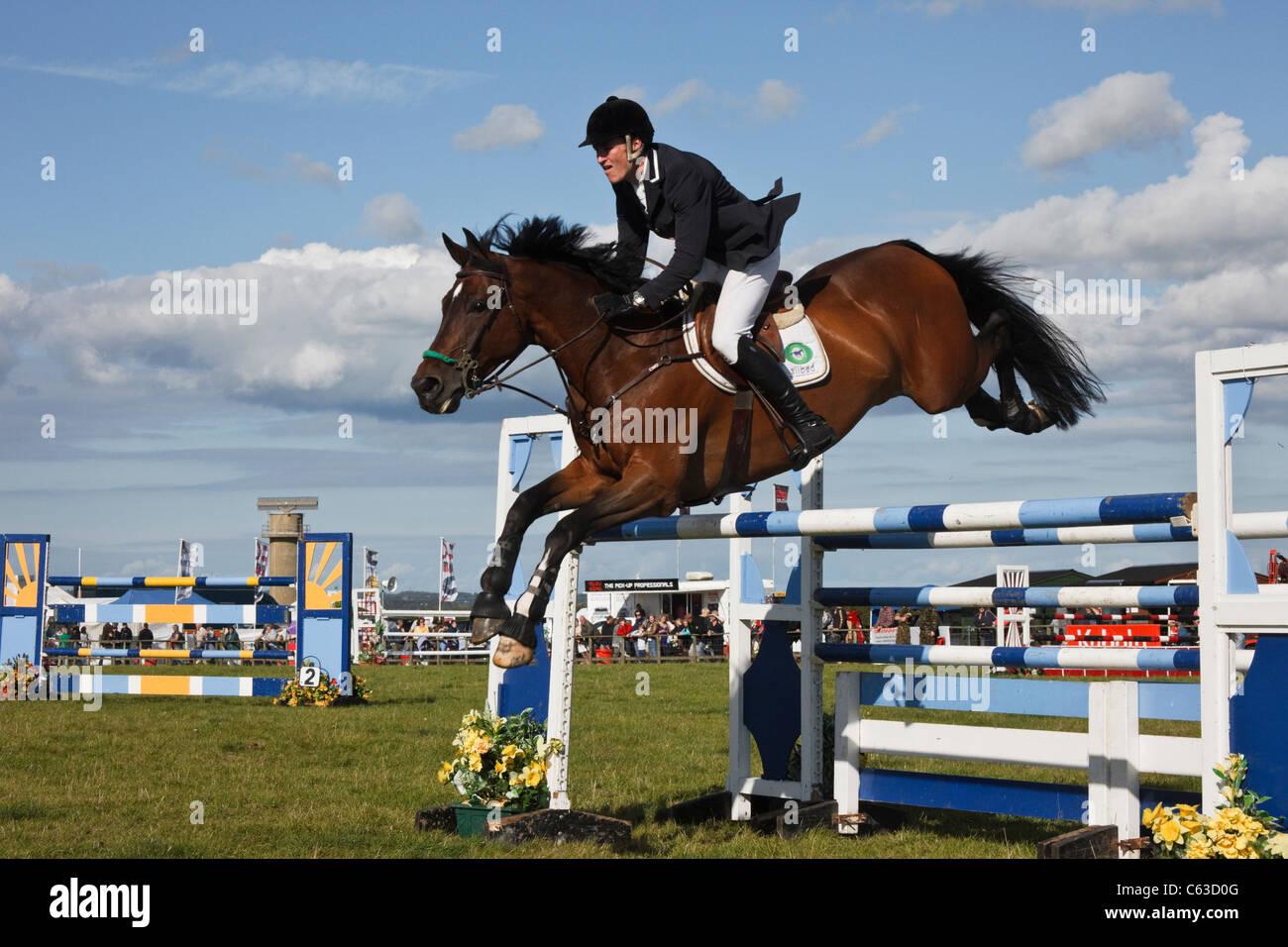 El norte de Gales, Reino Unido. Evento hípico internacional con caballo y jinete borrando los saltos en Anglesey Imagen De Stock