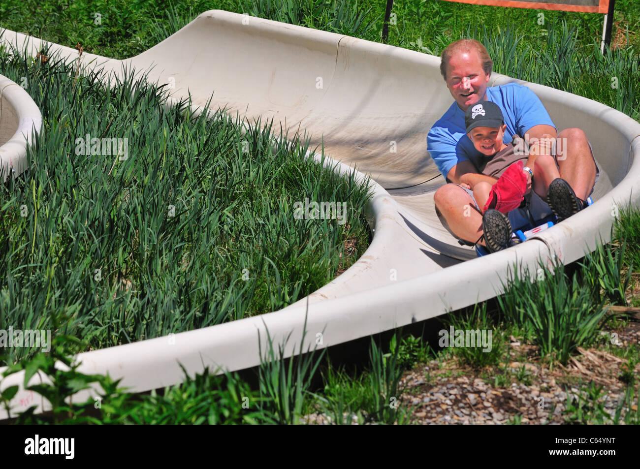 Un padre y su hijo disfrute de la velocidad de la Alpine Slide en Snowbird Ski and Summer Resort Imagen De Stock