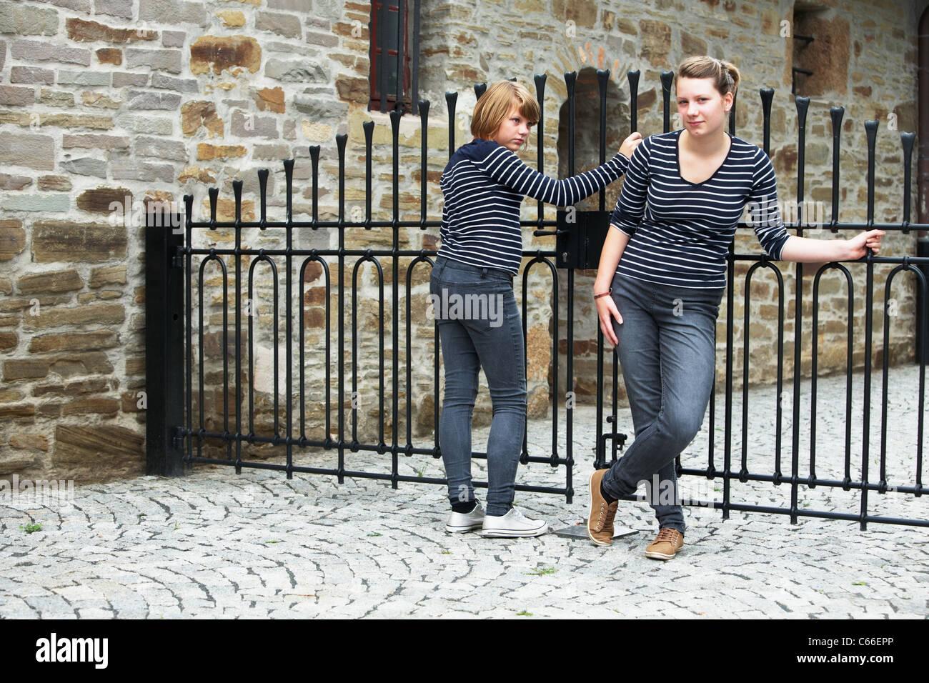 Dos niñas de pie delante de la puerta cerrada Foto de stock