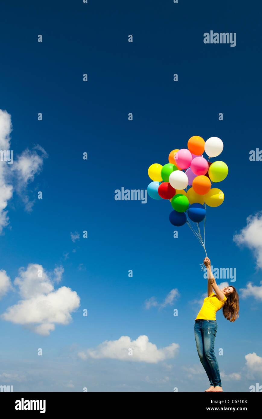 Mujer joven feliz con globos de colores en una pradera verde Imagen De Stock