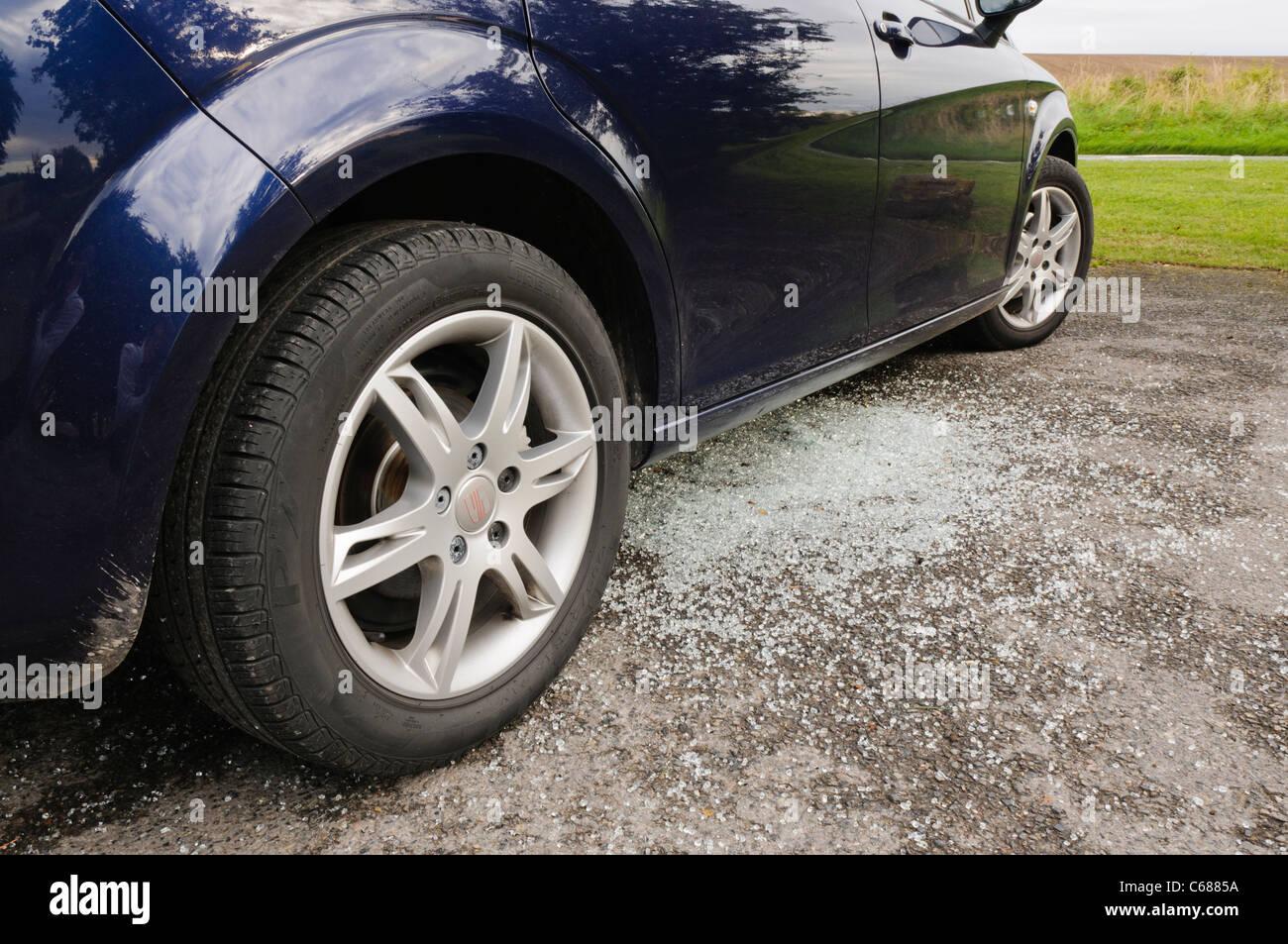 Vidrio roto debajo de un coche después de su ventana es golpeado por los ladrones Imagen De Stock
