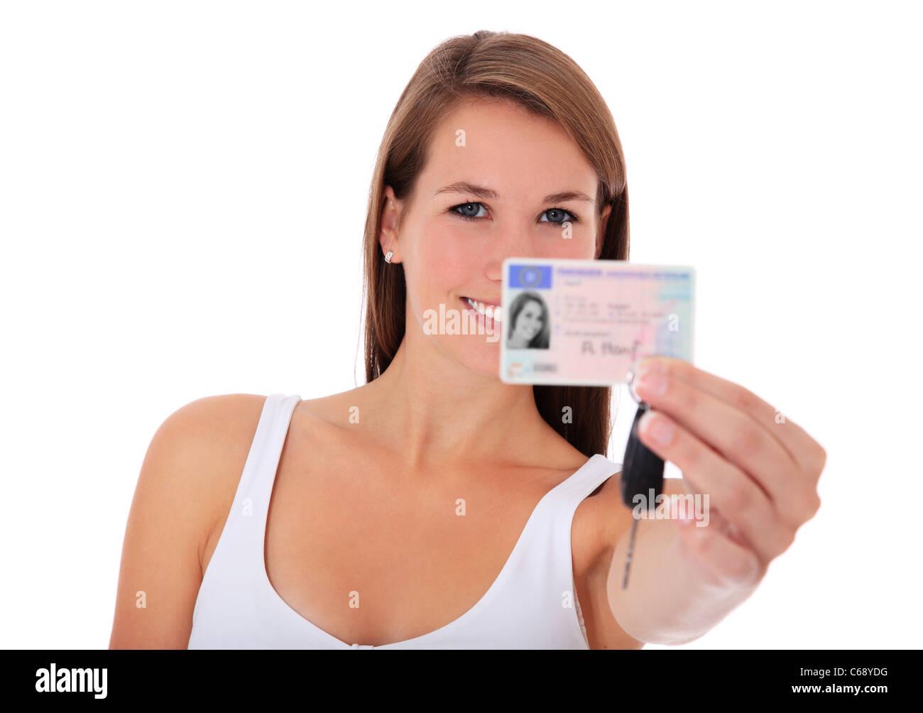 Mujer joven presentando su licencia de conductor. Todo sobre fondo blanco. Imagen De Stock