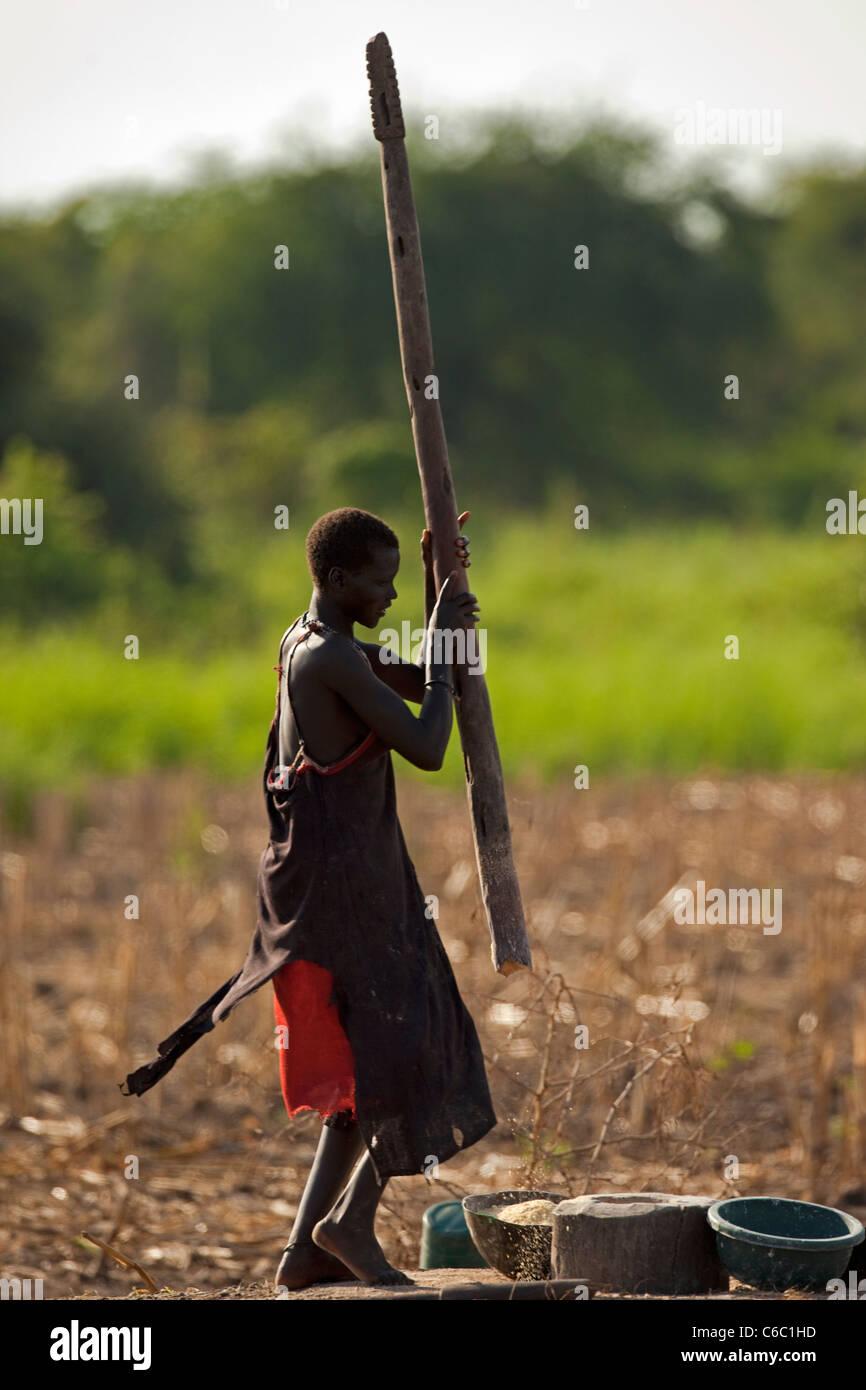 Las mujeres tribales golpeando las semillas de maíz Etiopía Imagen De Stock