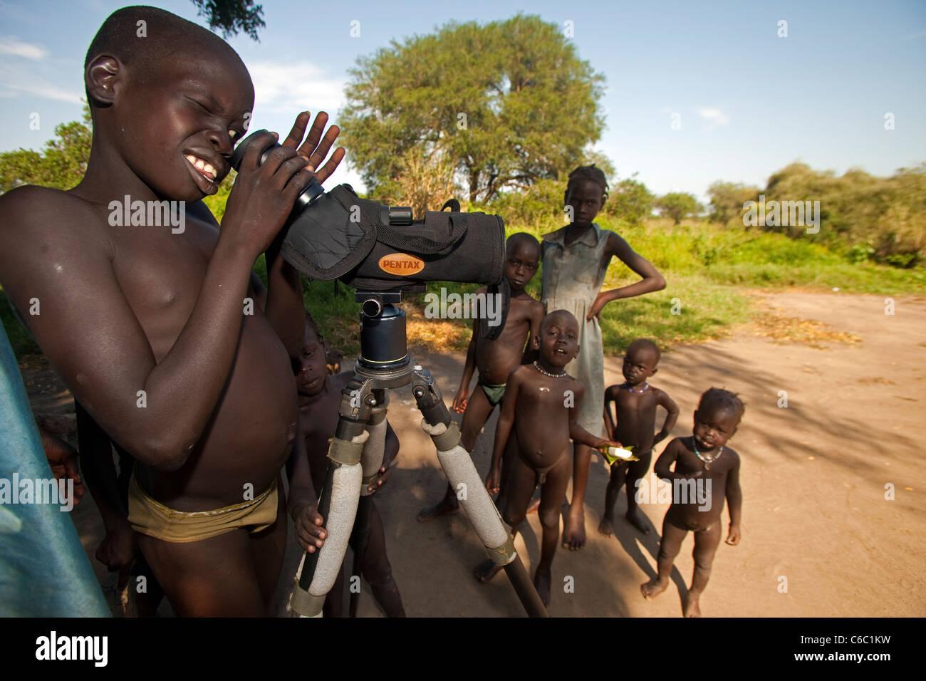 Los niños de las tribus comprobando con telescopio Etiopía Imagen De Stock