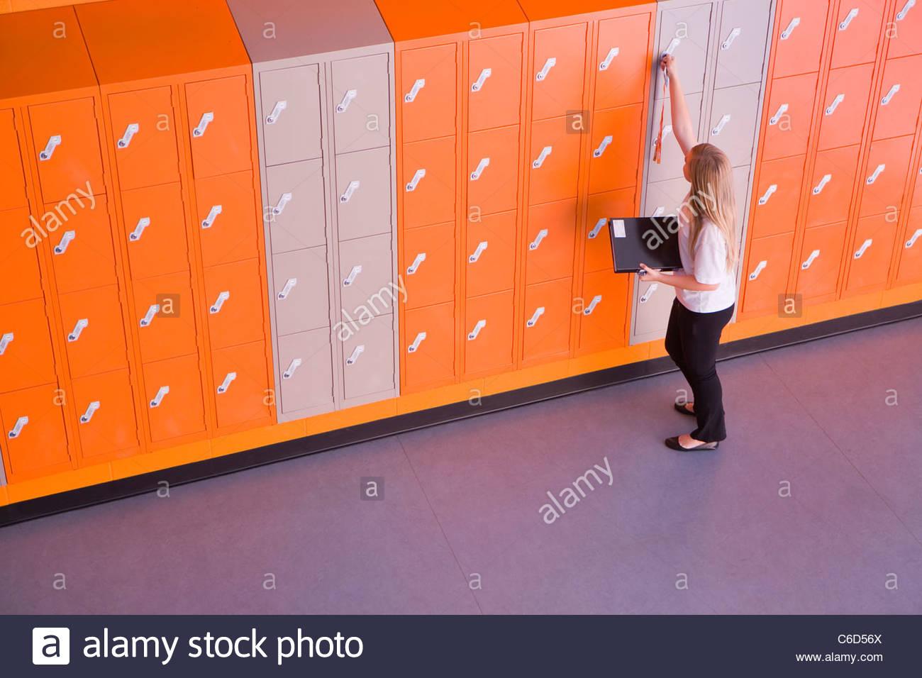 Chica locker de apertura en la escuela pasillo Imagen De Stock