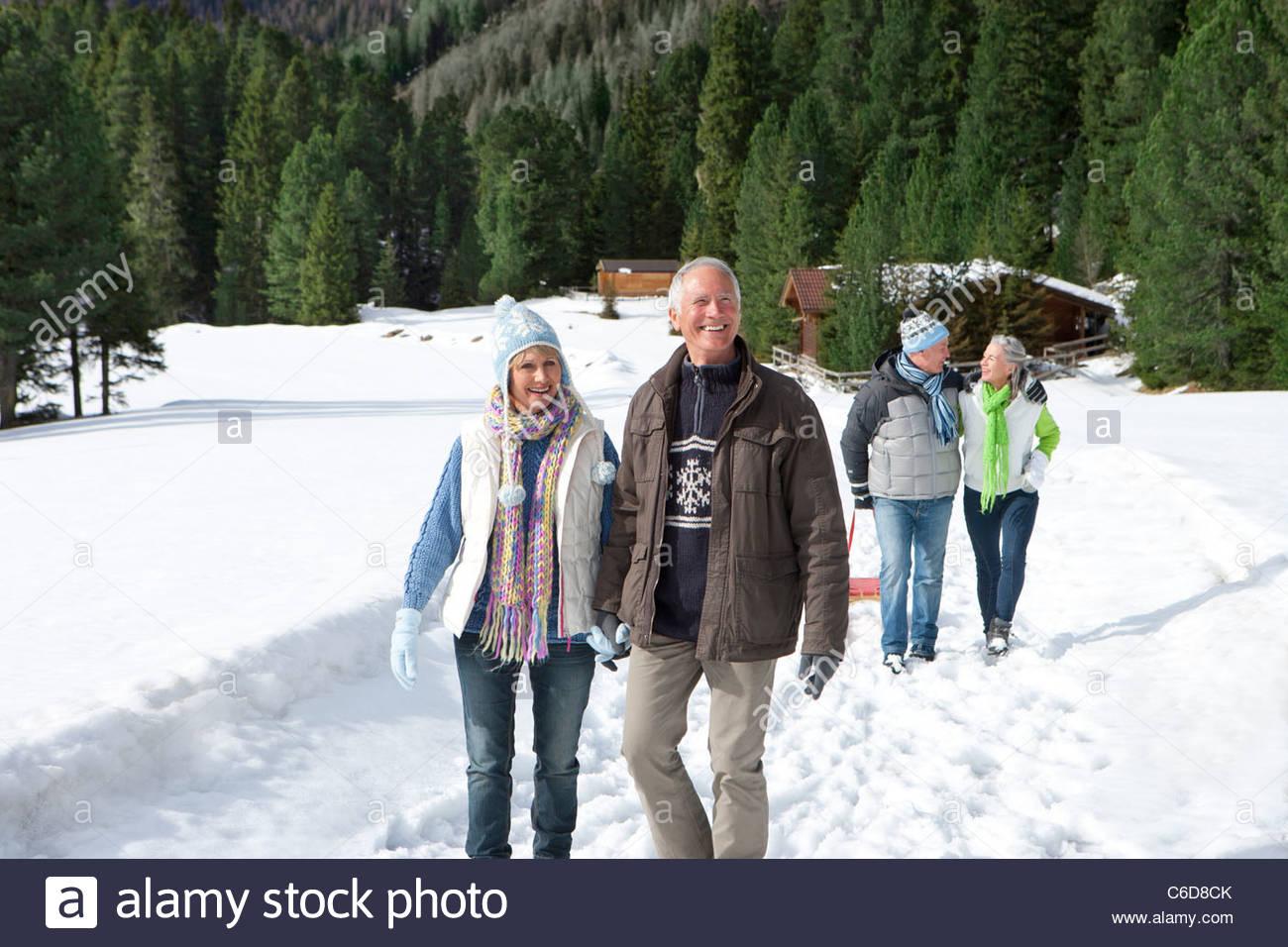 Los matrimonios tomados de la mano y caminar en el bosque cubierto de nieve fuera de cabañas Foto de stock