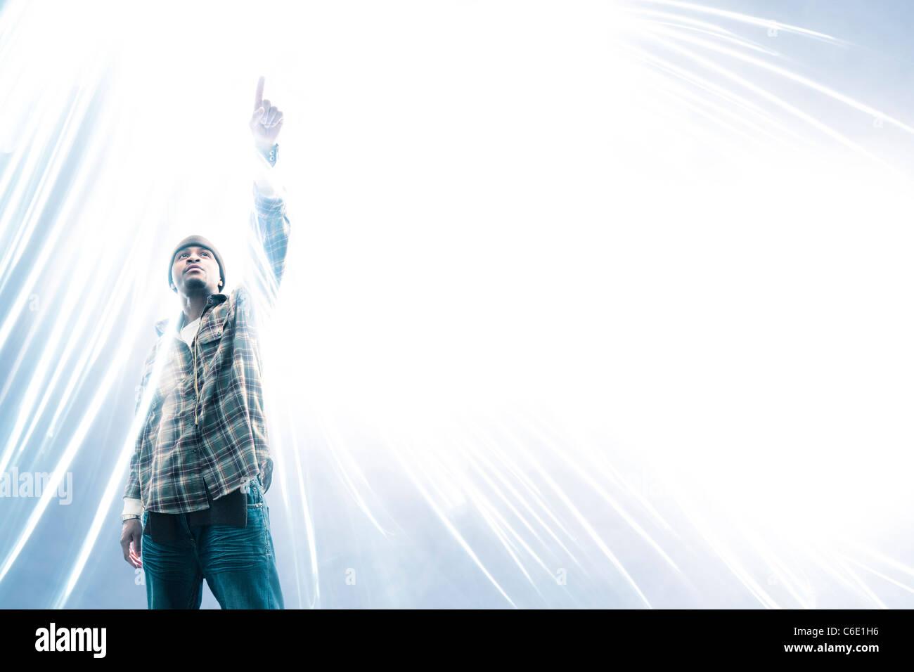 Hombre afroamericano apuntando a la chispa de luz Foto de stock