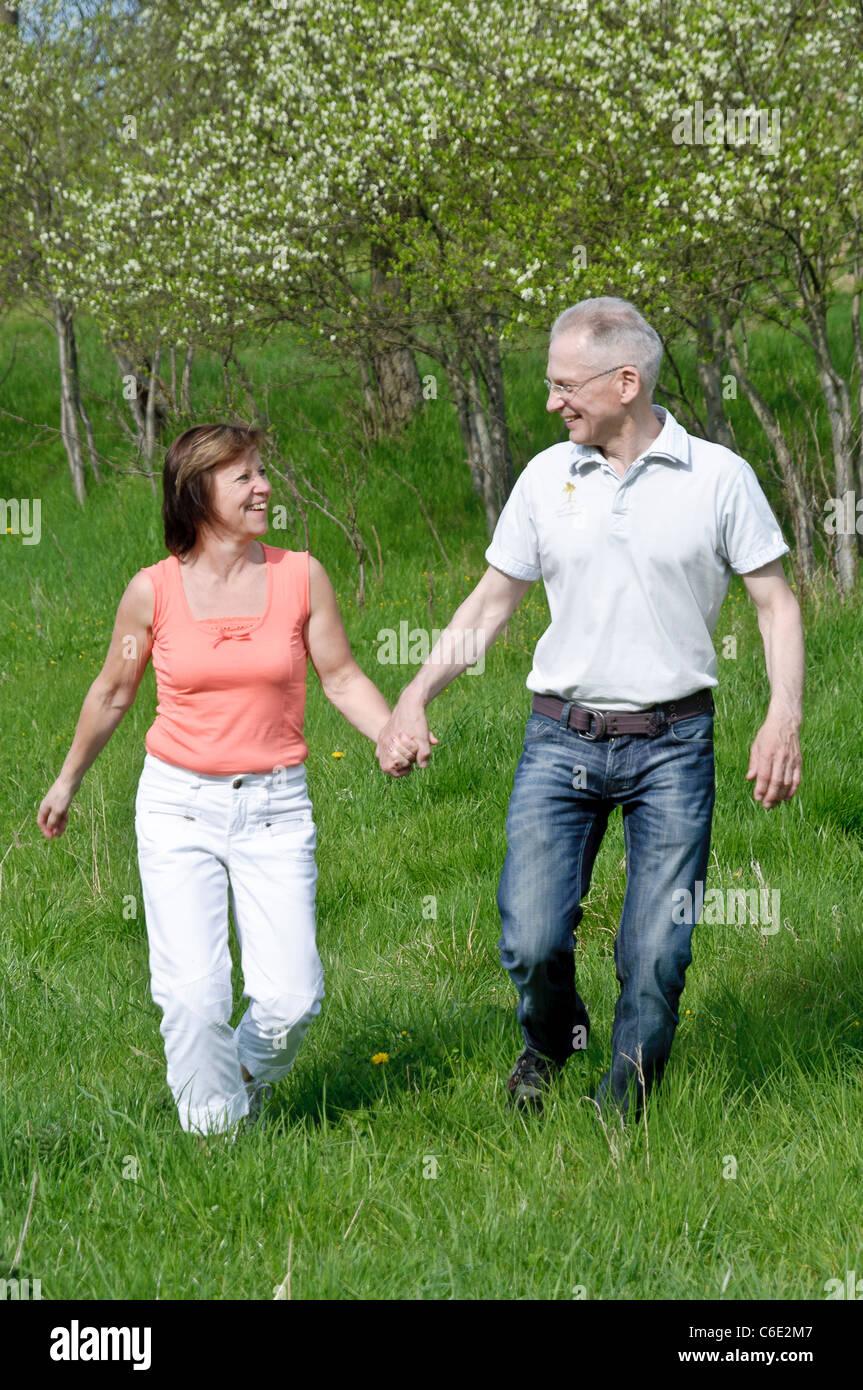 Pareja de mediana edad caminando de la mano en un prado Imagen De Stock