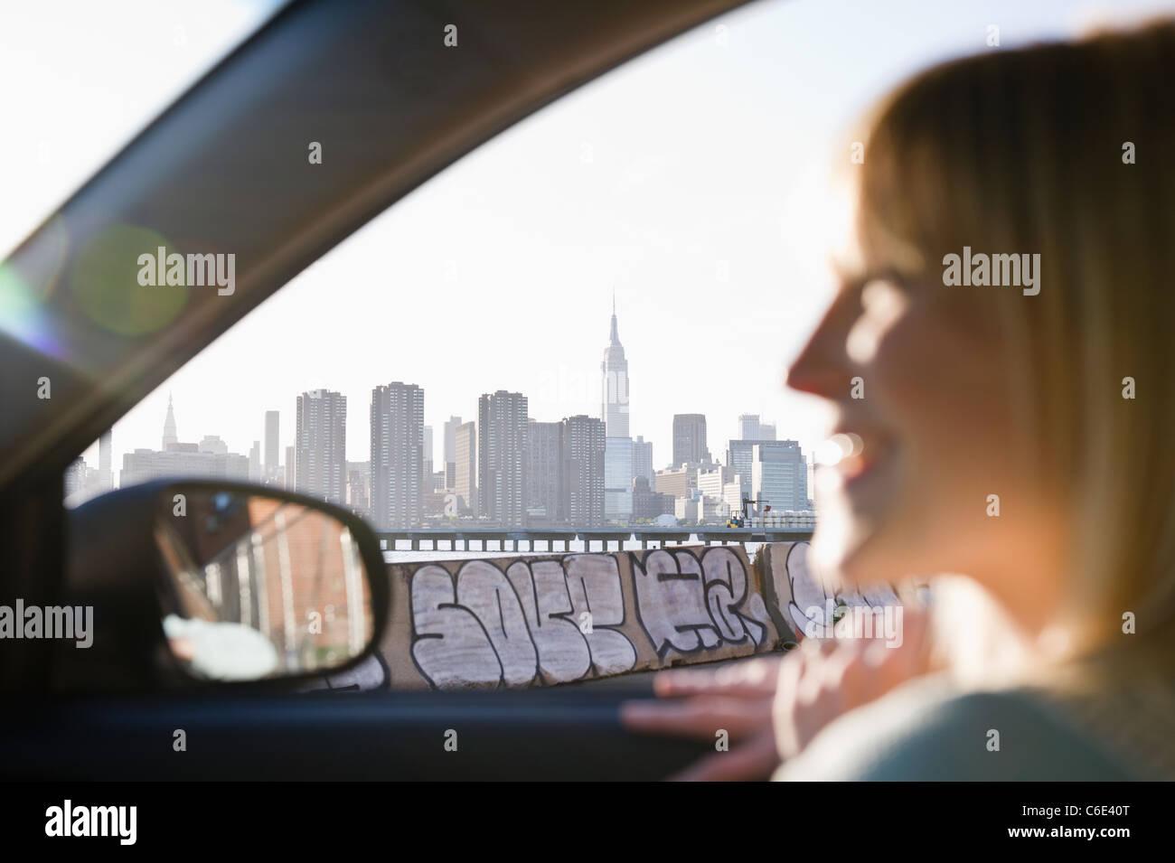 Ee.Uu., Brooklyn, Williamsburg, mujer conduciendo a través de la ciudad Foto de stock