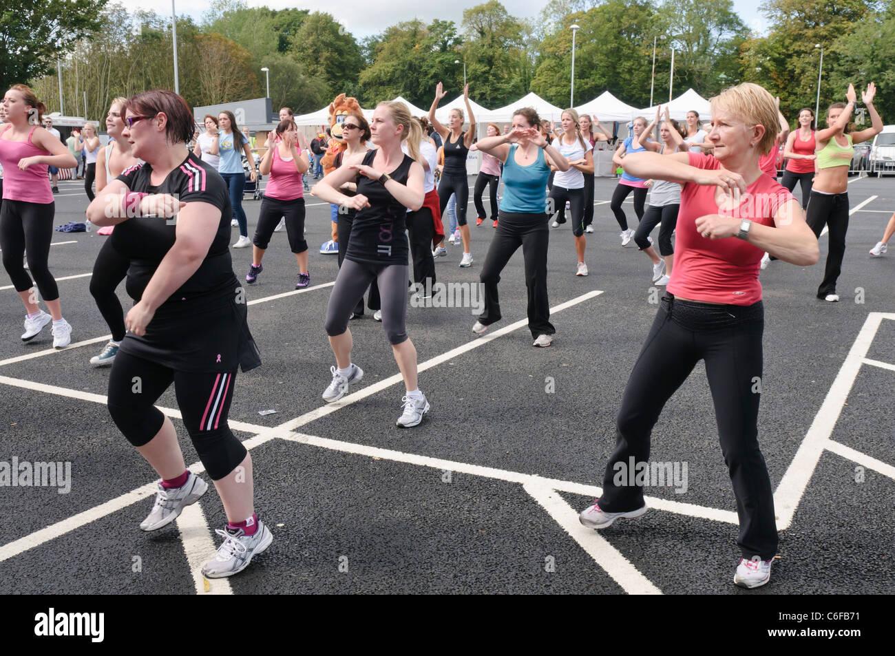 Gran número de señoras participar en una clase de Zumba exterior Imagen De Stock