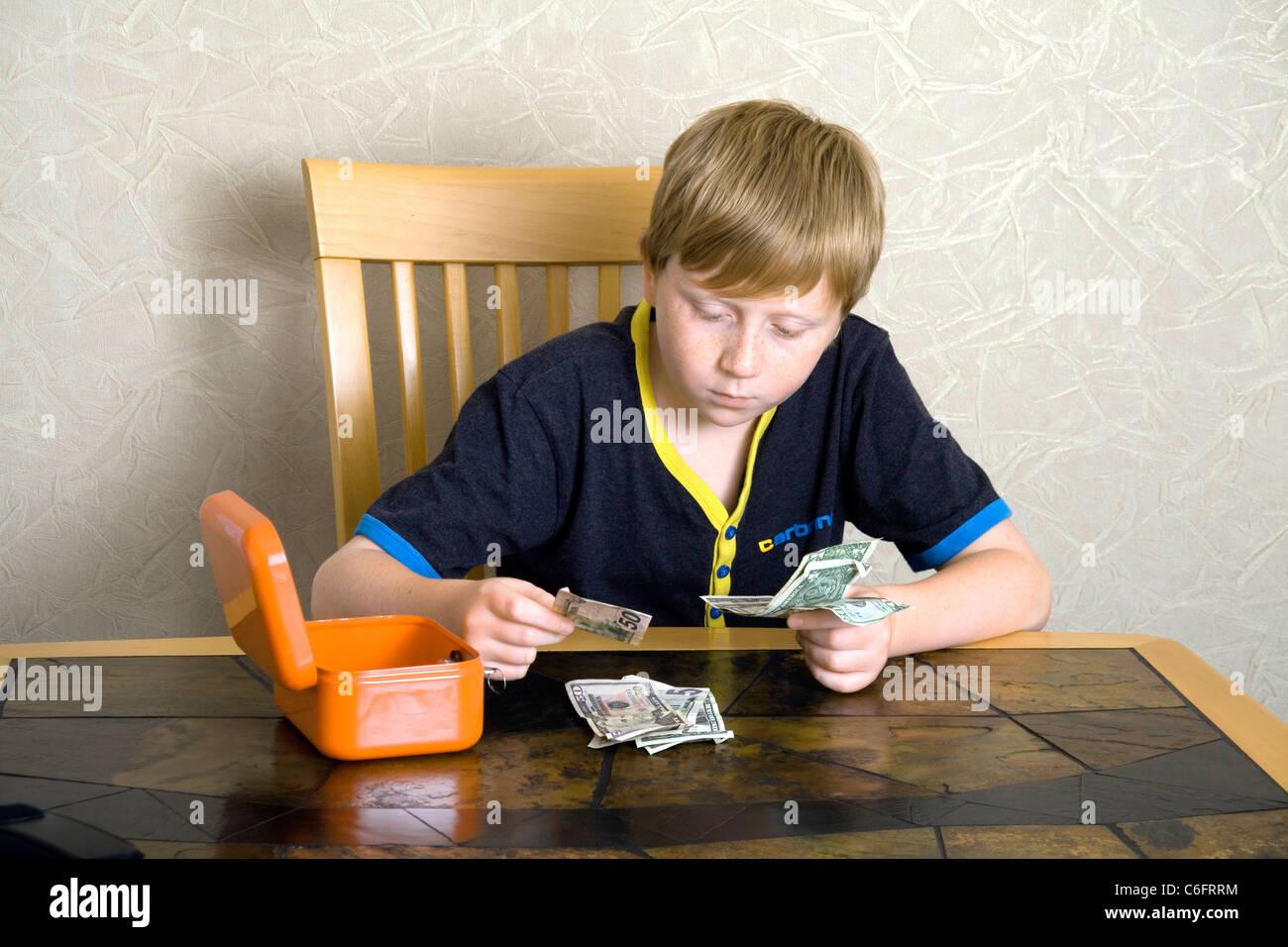Un muchacho de 12 años contando Dólares americanos Imagen De Stock
