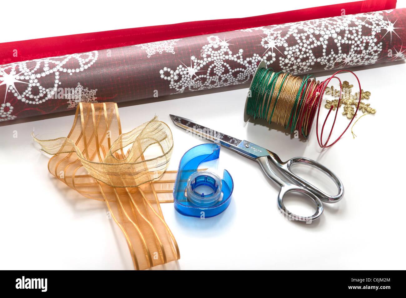 Papel de regalo de navidad con tijeras y cinta de cinta en un fondo blanco. Imagen De Stock