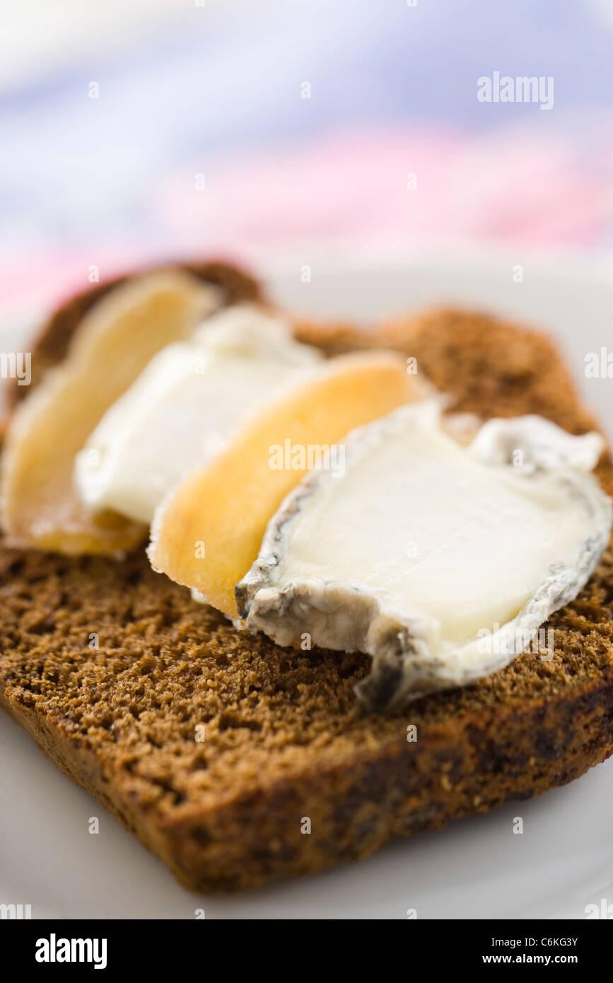 Rodajas de pan de jengibre con queso de cabra y gengibre confitado Foto de stock