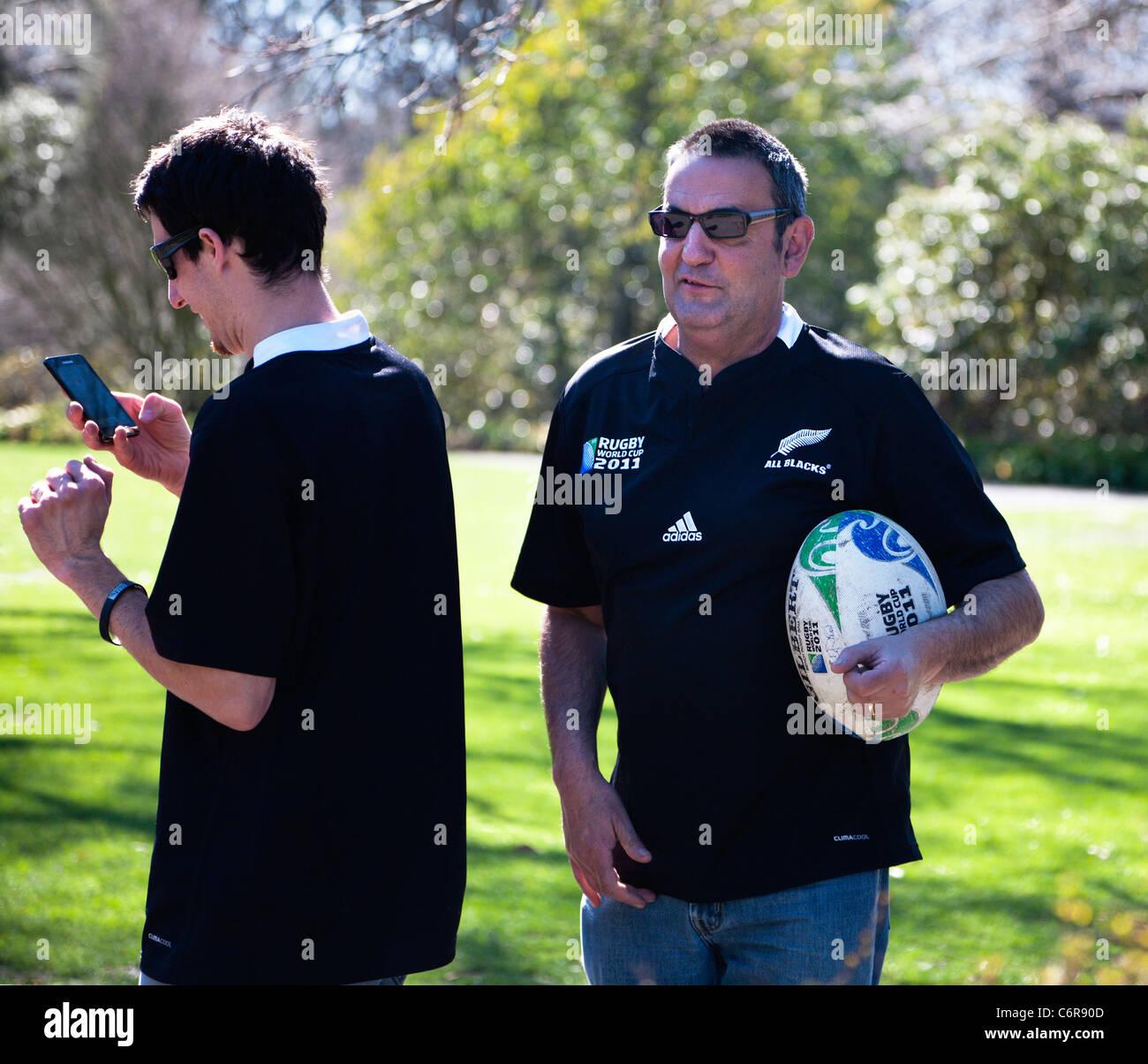 Dos Rugby World Cup 2011 simpatizantes portando Nueva Zelanda All Blacks camisetas. Uno sosteniendo un balón Imagen De Stock