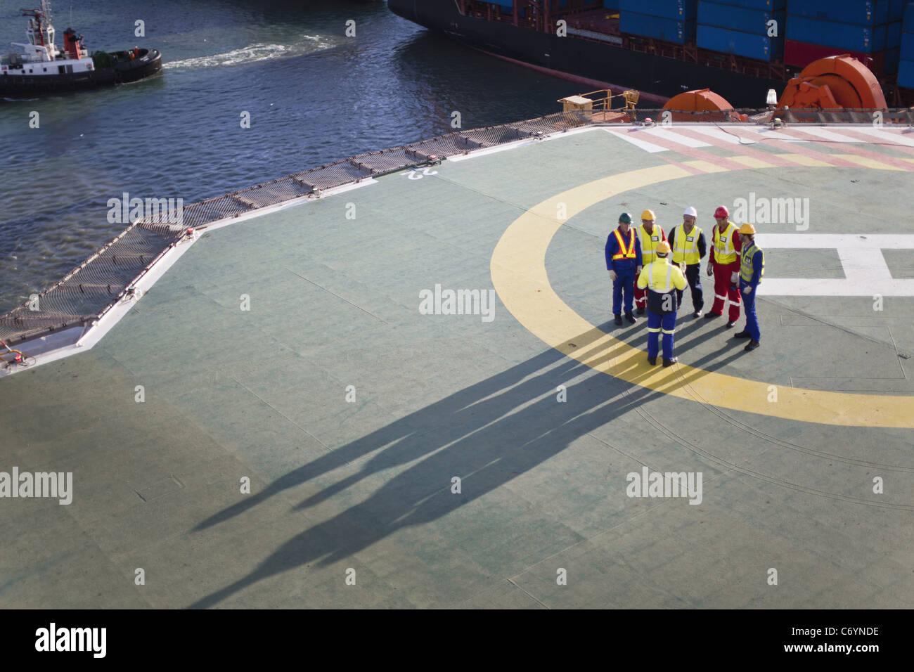 Los trabajadores hablando sobre el helipuerto de plataforma petrolífera Imagen De Stock