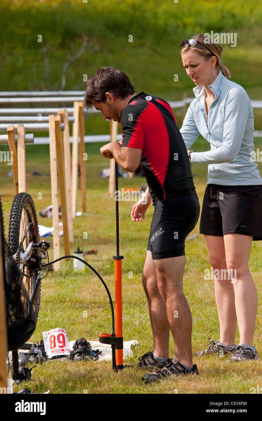 Macho mountain bike racer repara llanta desinflada durante apagado-carretera triathlon carrera Imagen De Stock
