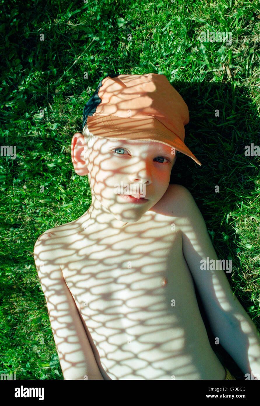Chico sentando en la sombra del eslabón de la cadena cerco Imagen De Stock