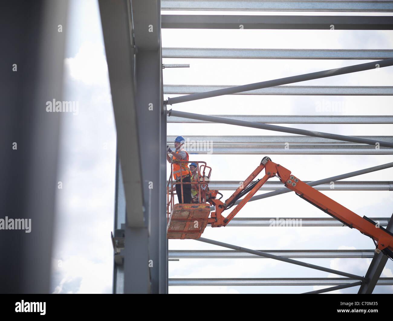 Los trabajadores de la construcción en cherry picker Imagen De Stock