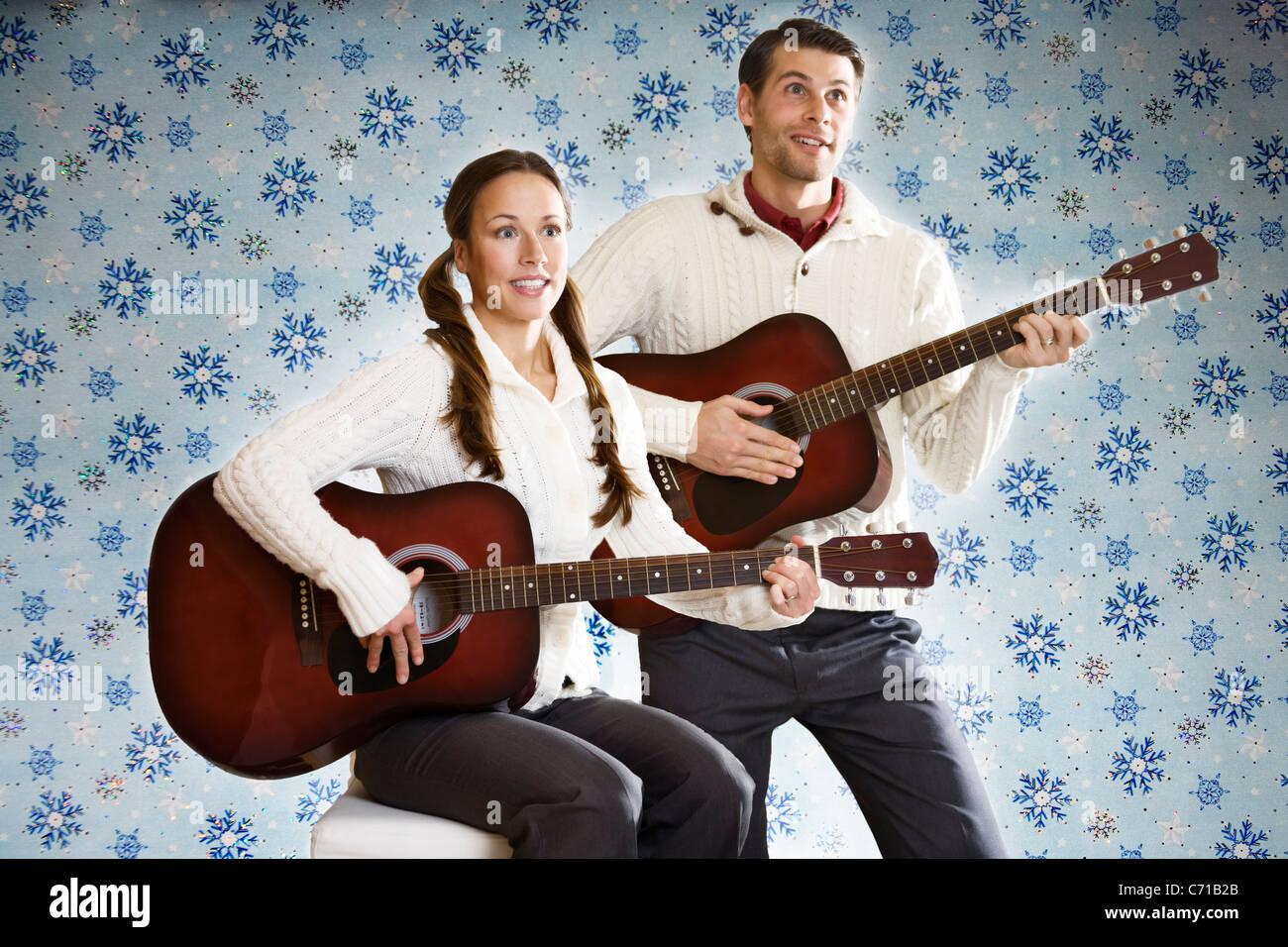 Un simulacro de Navidad portada del álbum ofrece una hilarante pareja joven la celebración de guitarras. Imagen De Stock