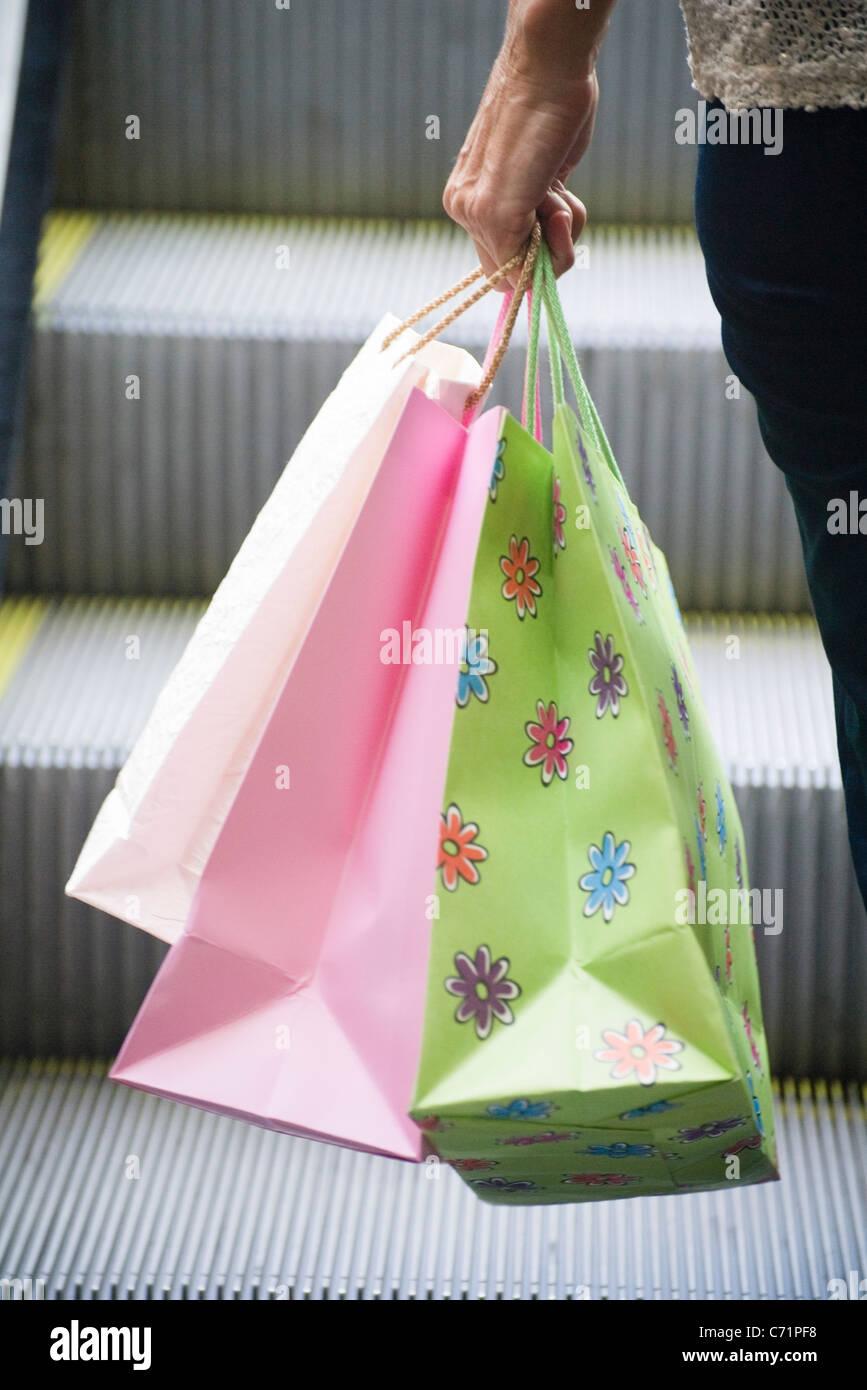 Persona llevar bolsas de la compra. Imagen De Stock