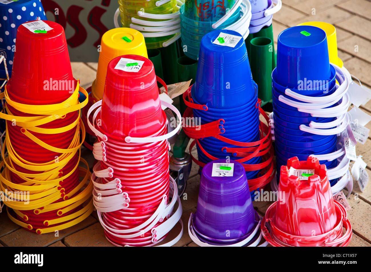 Coloridos juguetes infantiles playa cucharas de plástico en la pantalla  fuera de una tienda junto al 071f0dae2780d