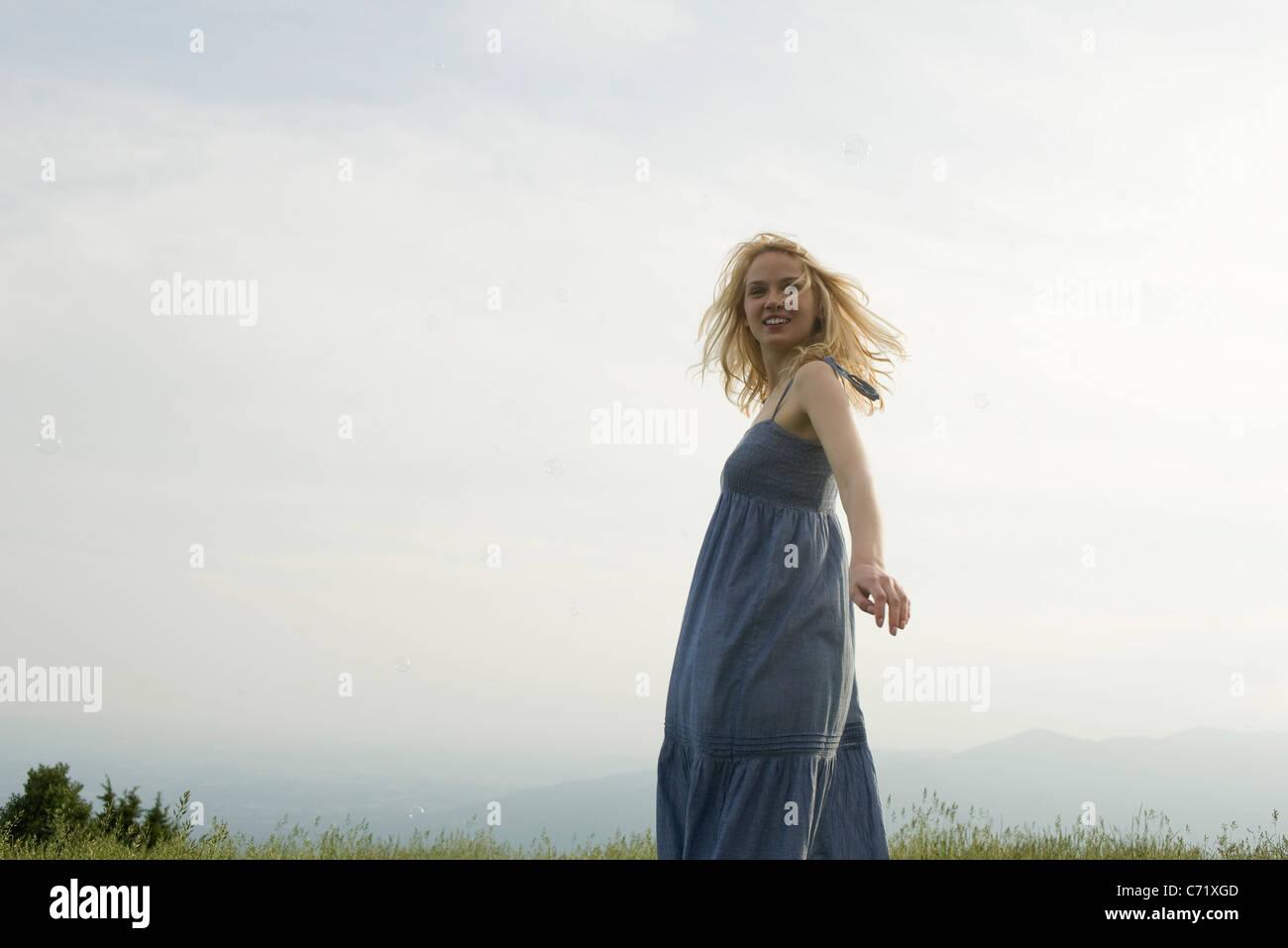 Mujer joven en praderas permanentes en días ventosos, burbujas flotando a su alrededor. Foto de stock