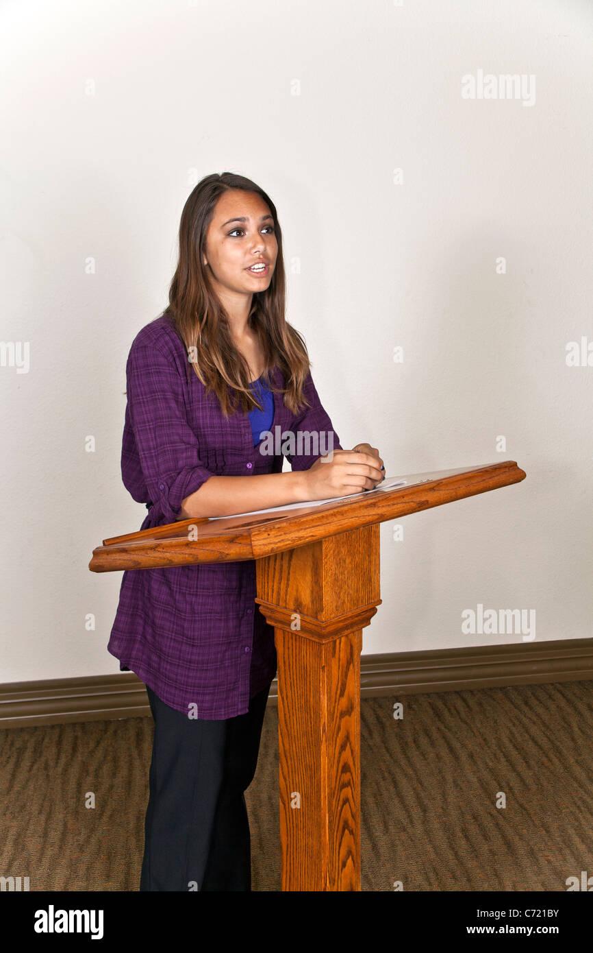 Teen chica hispana hablando en público del atril en frente de la clase. Señor © Myrleen Pearson Imagen De Stock