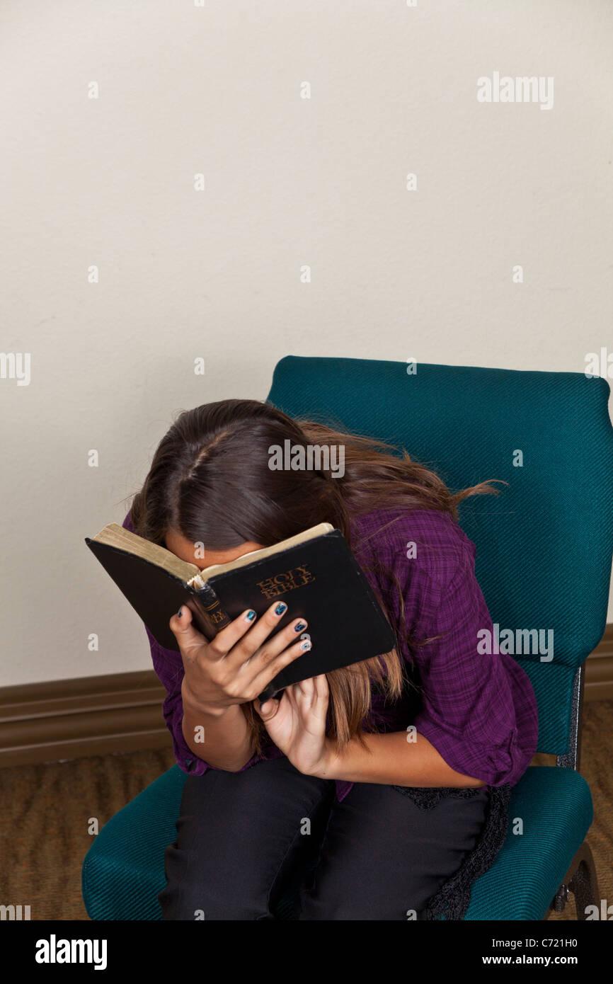 Teen chica hispana meditando la lectura de la Sagrada Biblia con emotioon emocionalmente. Señor © Myrleen Imagen De Stock