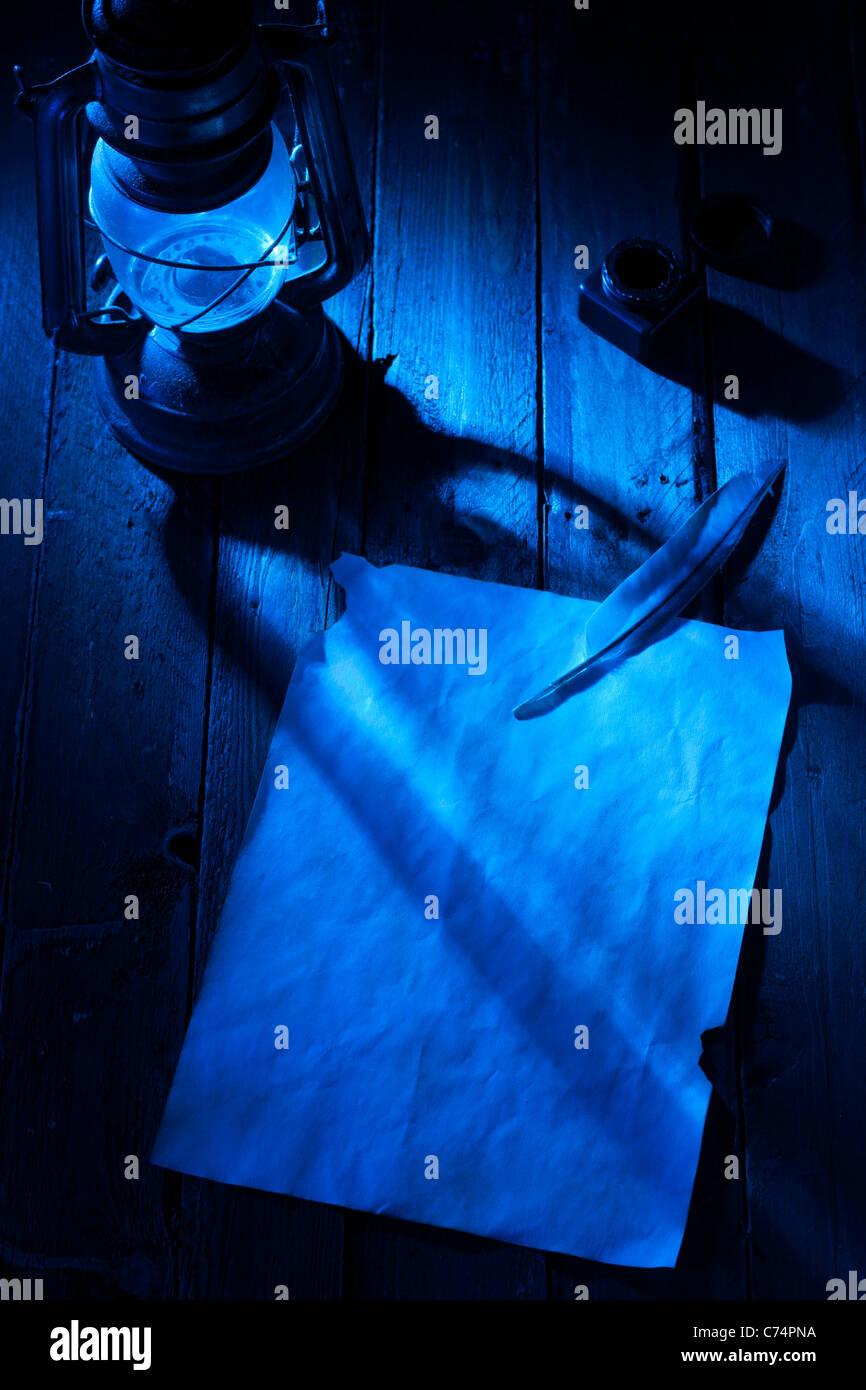 Hoja de papel en blanco con pluma y tinta, linterna en la noche Imagen De Stock
