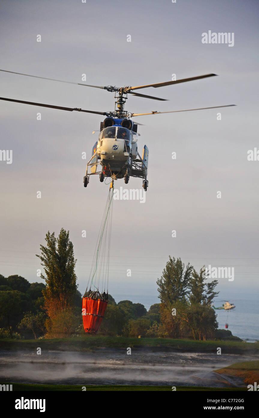 Kamov Ka-32A11BC helicóptero recogiendo agua, Cabopino Golf, Costa del Sol, Málaga, Andalucía, España, Europa Occidental. Foto de stock