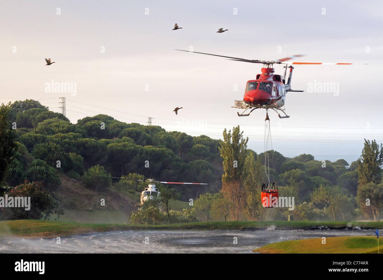 Helicóptero Bell 412 recogiendo agua, Cabopino Golf, Costa del Sol, Málaga, Andalucía, España, Europa Occidental. Foto de stock