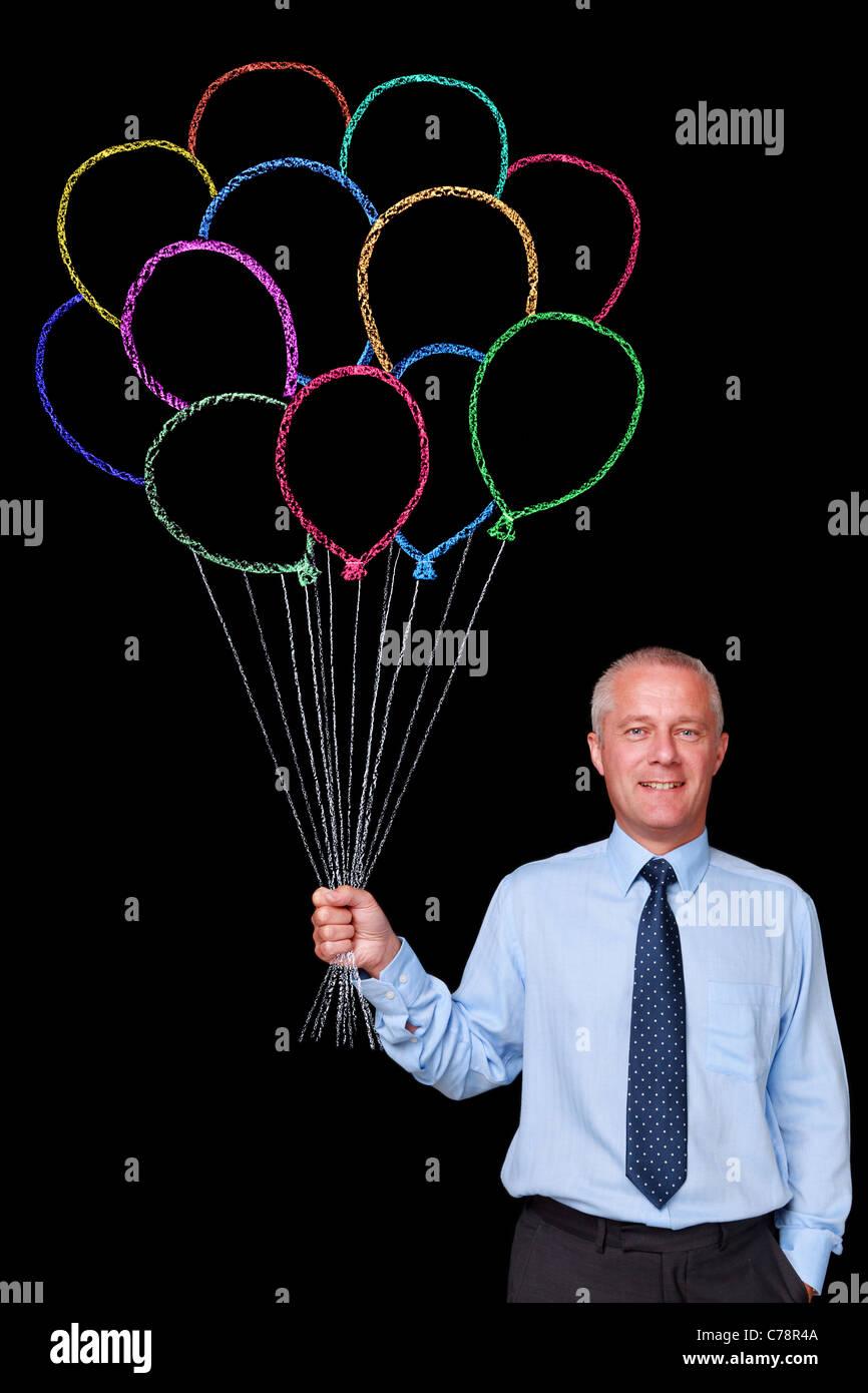 Foto de un empresario maduro contra un fondo negro sosteniendo un gran montón de tiza dibujado globos Imagen De Stock