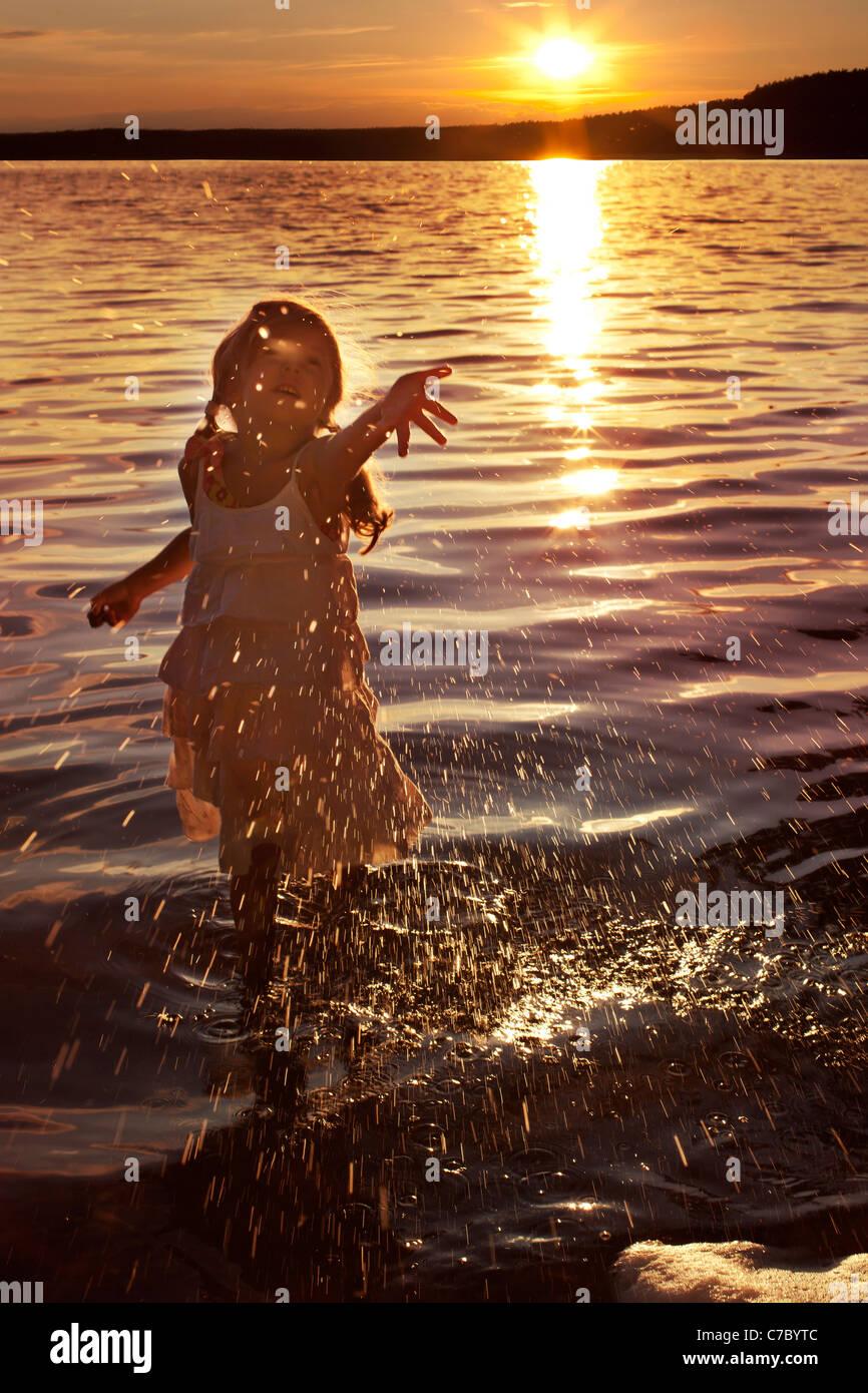 Poco feliz, la niña salpicaduras de agua en el lago Imagen De Stock