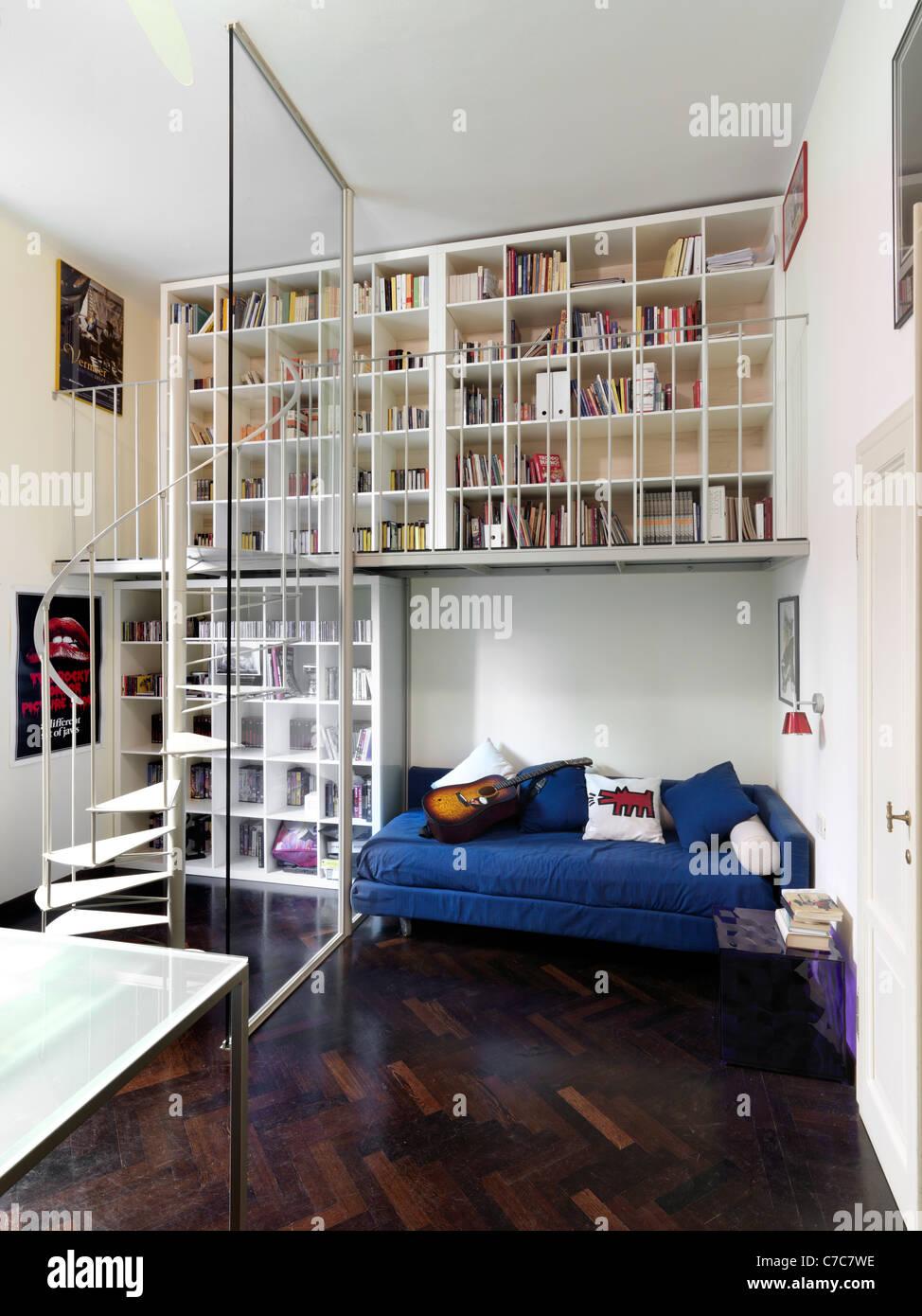 Dormitorio moderno con piso de madera y estantería encima de la cama Imagen De Stock