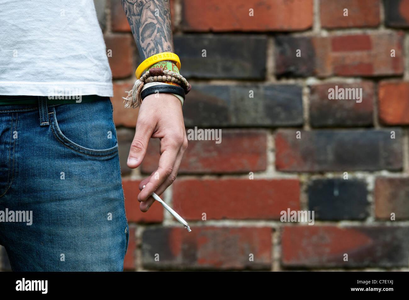 Tatuadas adolescente sosteniendo un porro de marihuana Foto de stock