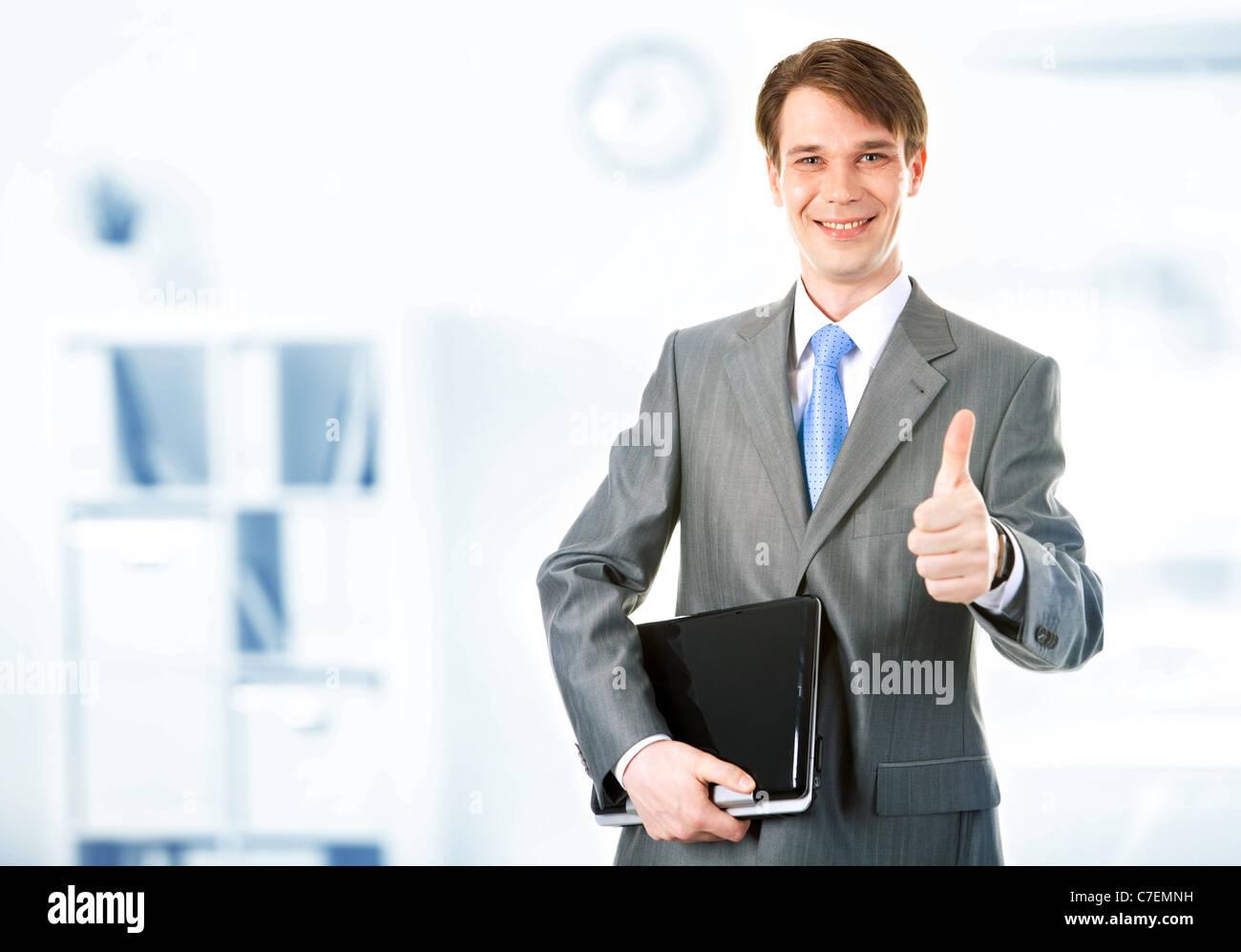 Retrato de feliz empresario mantiene el portátil y mostrando el pulgar hacia arriba Imagen De Stock