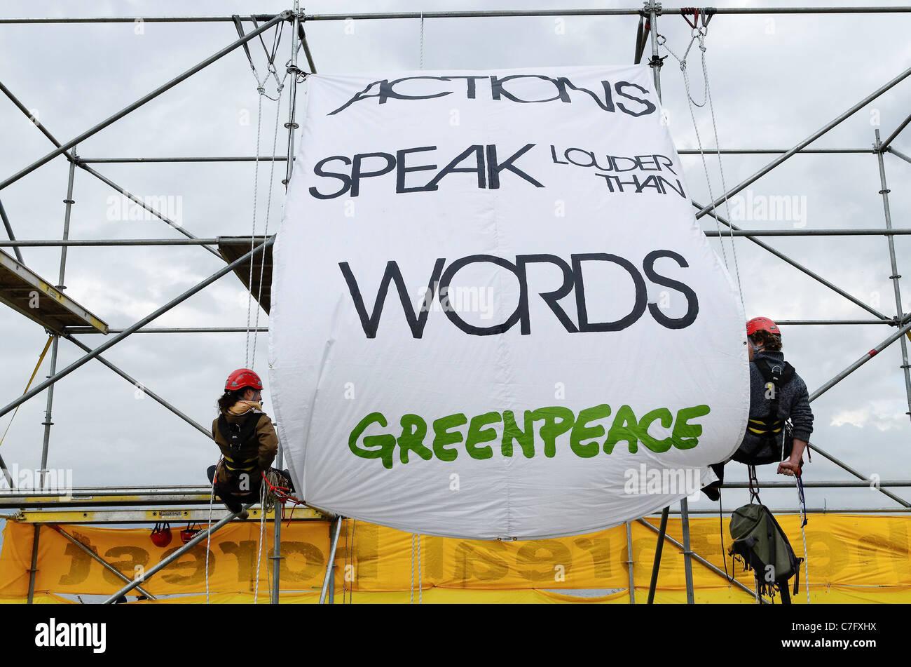 """Activistas de Greenpeace despliegan pancarta 'Las acciones hablan más que las palabras"""" Imagen De Stock"""