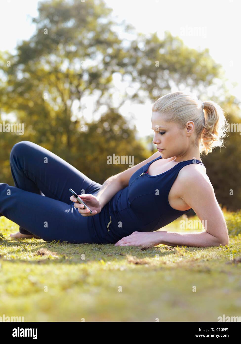 Una mujer en ropa deportiva sentados en el césped leyendo un mensaje de texto Imagen De Stock